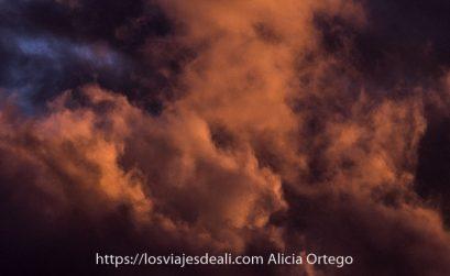 grandes nubes coloreadas por puesta de sol en naranja y malva para ilustrar post de novela policíaca, de suspense y novela negra