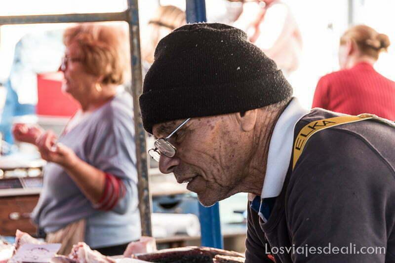 pescadero con gorro de lana y gafas preparando pedido de un cliente