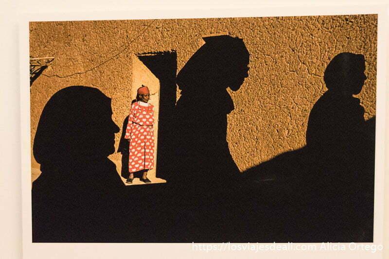 fotografía de Marruecos donde se ve a una mujer en la puerta de su casa de adobe y la sombra de otras 3 mujeres pasando delante xpuesta en el CPF de Oporto