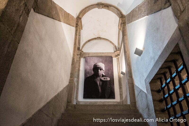 escaleras del centro portugués de fotografía y al fondo foto antigua de un niño preso con el número 47 en gran tamaño colgada en la pared