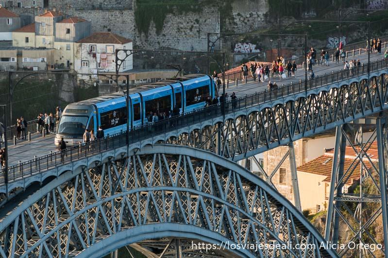 paseo superior del puente luis I con gente andando y un tranvía