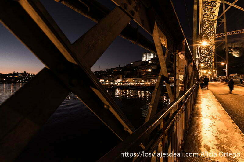 caminando por el paso inferior del puente Luis I al anochecer viendo la ciudad entre los huecos de la estructura