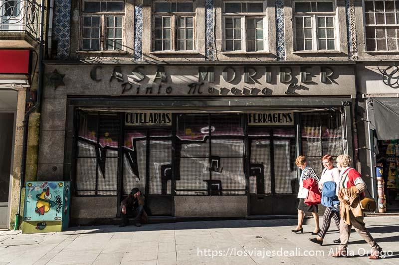 tres mujeres pasando andando delante de una tienda antigua en la rua de las flores uno de los lugares que ver en oporto