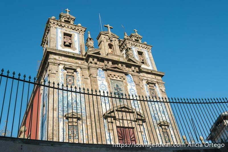 iglesia de san ildefonso con fachada de azulejos y dos campanarios barrocos en paralelo uno de los lugares que ver en oporto