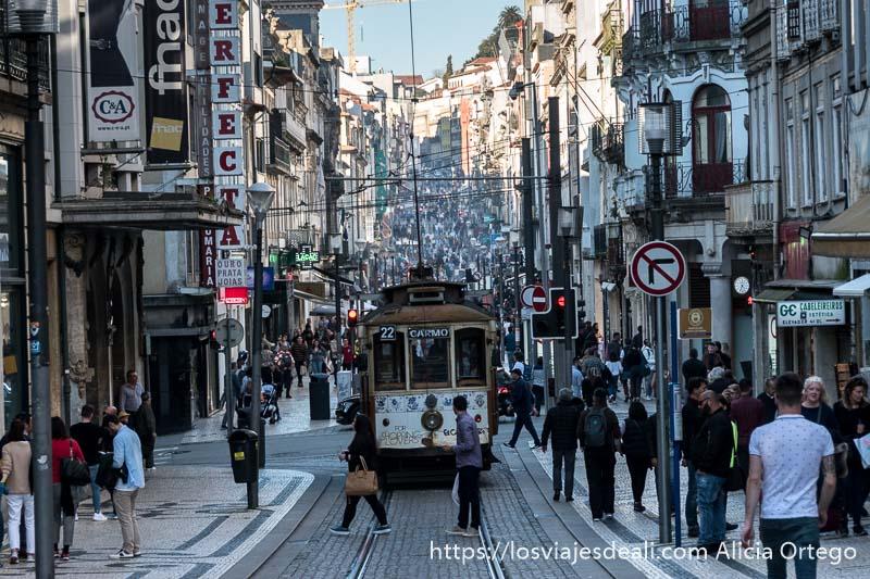 rua de santa catarina con un tranvía y mucha gente caminando uno de los lugares que ver en oporto