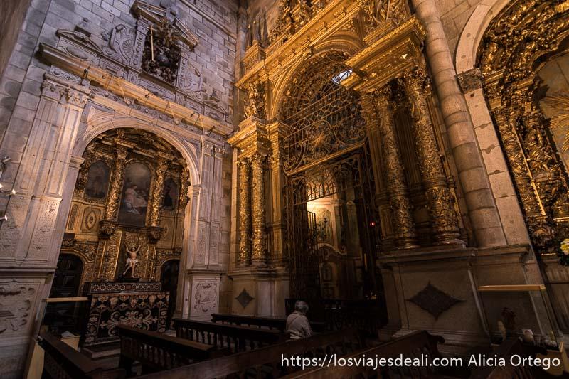 interior de la sé de oporto con altar barroco recubierto de oro y una mujer mayor rezando arrodillada