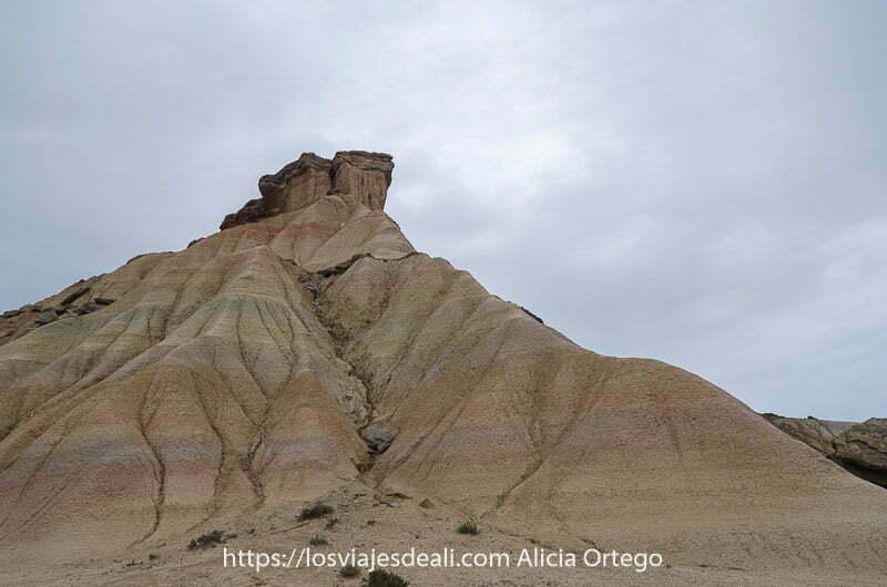 cabezo de las Bardenas Reales visto desde abajo con ondulaciones de arcillas y yesos de distintos colores