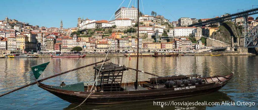 vista de la ribeira de oporto desde la orilla de enfrente con un barco de madera en primer plano