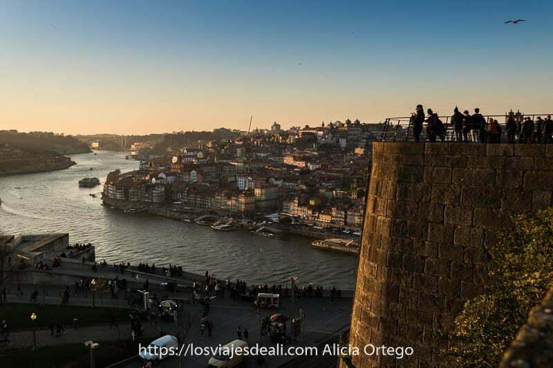 gente asomada al mirador para ver el río duero con la puesta de sol y oporto al fondo