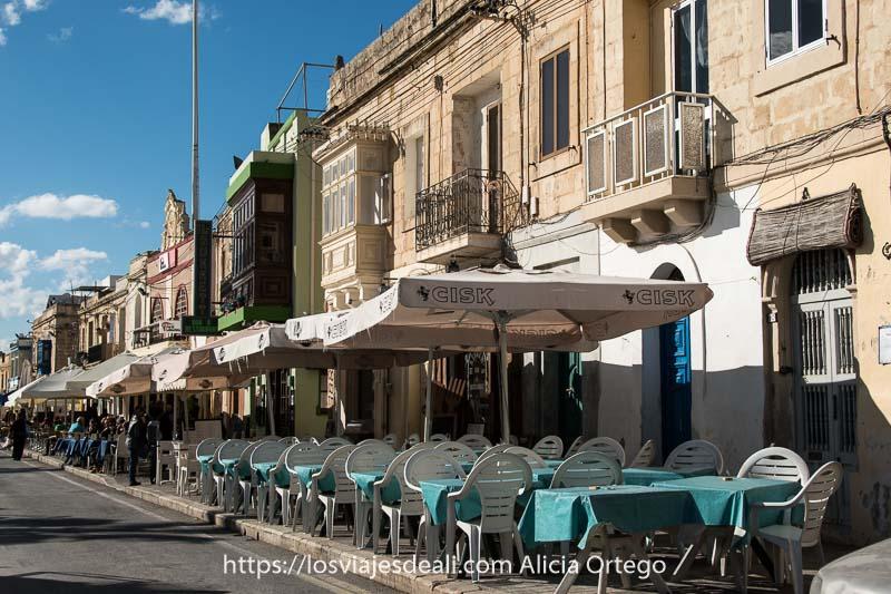 casas de la bahía de marksaxlokk con balcones típicos de malta y terrazas de restaurantes con sombrillas