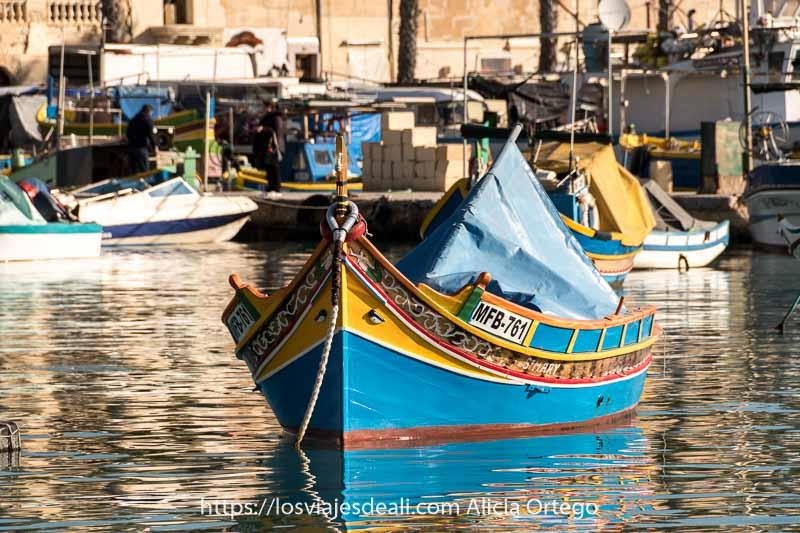 barca pintada de azul, amarillo y rojo con ojos de osiris en la proa anclada en el puerto de marksaxlokk