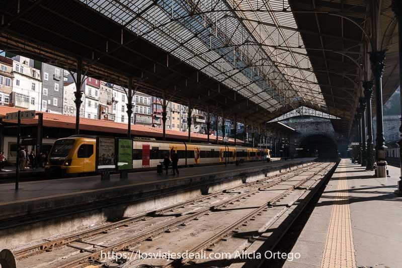 vías y andenes de la estación con un tren de cercanías entrando y techo de hierro con cristales