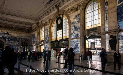 vestíbulo de la estación de são bento con gente admirando los paneles de azulejos