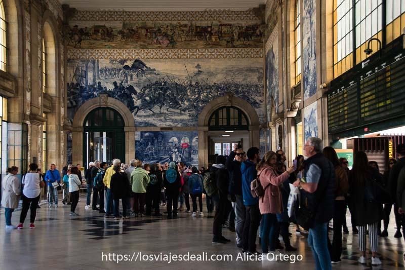vestíbulo de la estación de oporto con grupos de turistas escuchando a sus guías